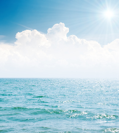 water ripple: white clouds in blue sky with sun and sea
