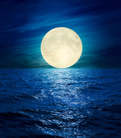 blue sea: big moon in clouds over night sea