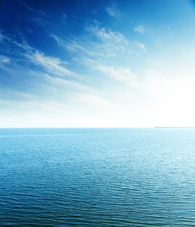 青空: 海の上の青い空に完璧な夕日。航空写真ビュー
