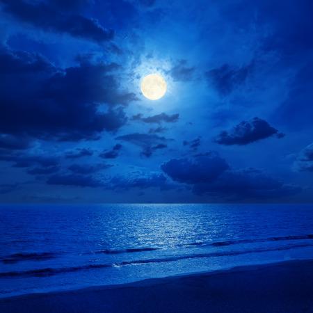 volle maan in bewolkte hemel en zee met reflecties