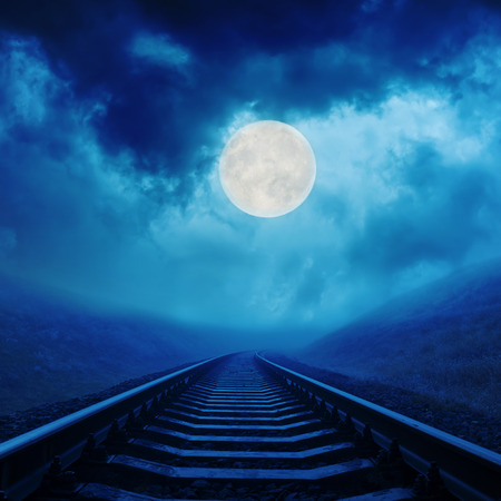 full moon in night clouds over railroad Stock Photo