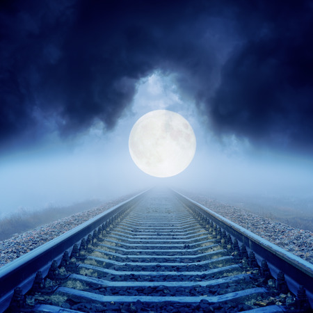 full moon over railroad in dark clouds