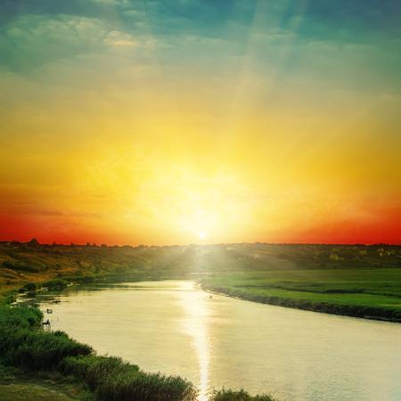 orange sunset: bright orange sunset over river