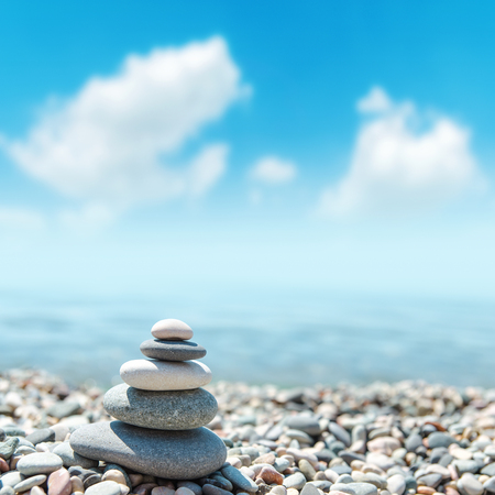 stack of rounded stones zen-like and blue sky with clouds. soft focus 版權商用圖片