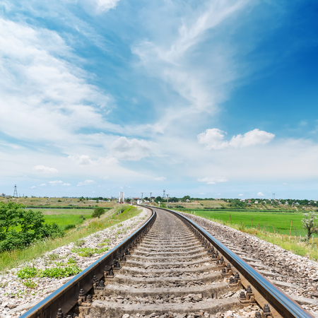 long way: railway to horizon in green landscape under white clouds