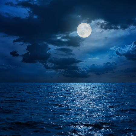 full moon in clouds over sea in night Stock Photo