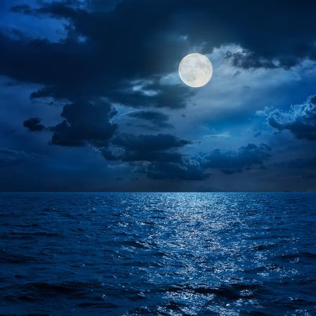Pleine lune dans les nuages ??sur la mer en nuit Banque d'images