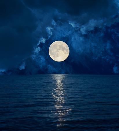 暗い雲の海の上の満月