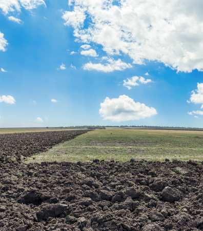 ploughed field in autumn and clouds in blue sky