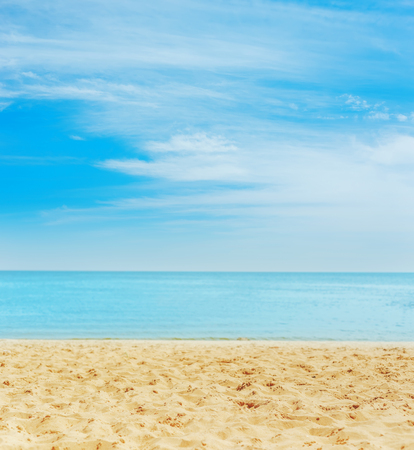 sand on the beach. sea on horizon and blue sky with clouds. soft focus on bottom of picture