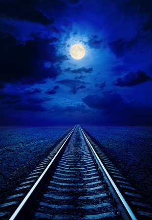 full moon in night sky with clouds over railroad in desert