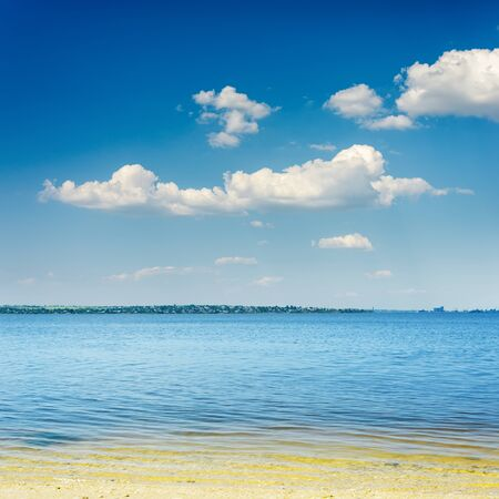 river beach with sand and blue sky with clouds over it