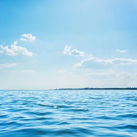 blauwe zee en lage wolken in de lucht erboven