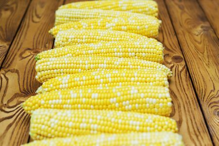 ripe yellow corn as background on wood table. soft focus