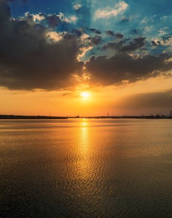 orange sunset in dramatic clouds over water in river Banco de Imagens - 129736174