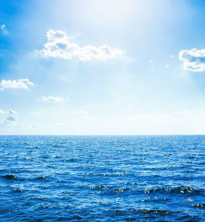 ciemnoniebieska woda w morzu i słońce z chmurami na niebie