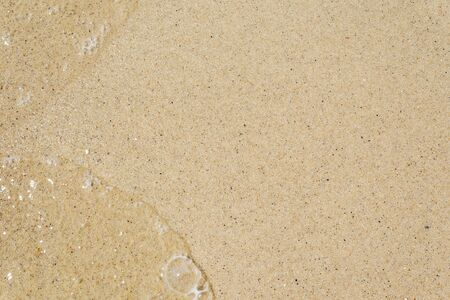 yellow sand close up as background. transparent water splash in left side Stock fotó