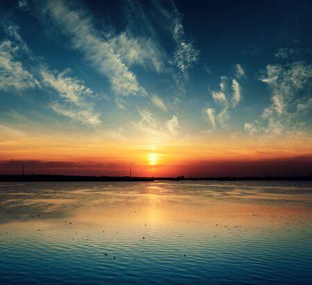 niedriger orangefarbener Sonnenuntergang in dramatischen Wolken über dem Fluss