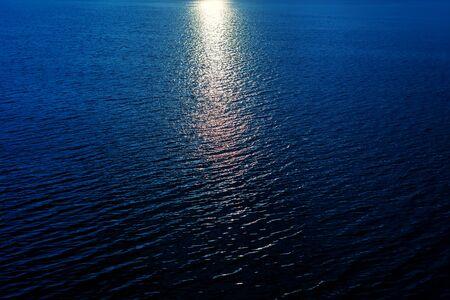 sun reflection in dark blue water in river Stock fotó