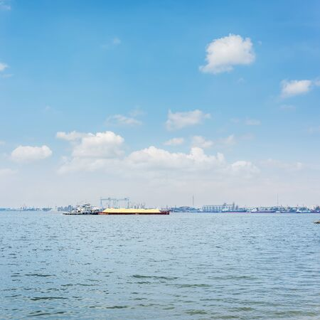 barge with sand in river. blue sky with clouds over water Stock fotó
