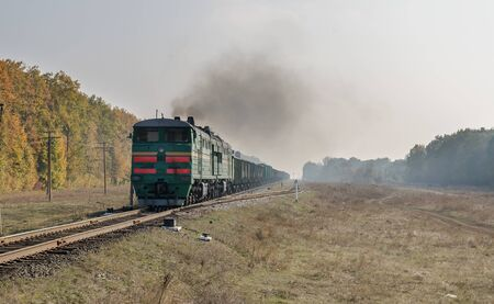 old locomotive with smoke pollution on railway