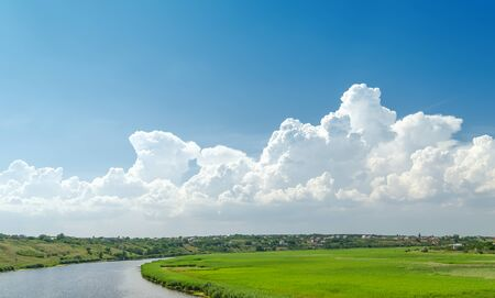 white clouds in blue sky over river and green meadow