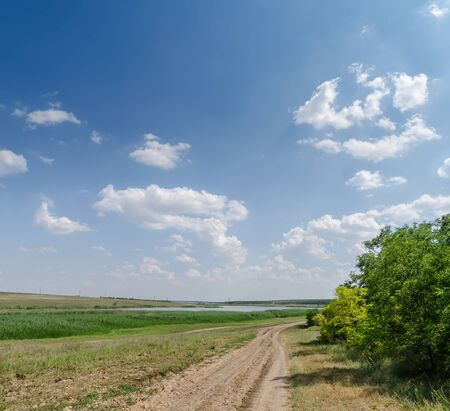 rural dirty road in green meadow and low clouds in blue sky