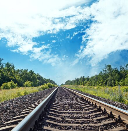 one railroad to horizon in green meadow and blue sky with clouds