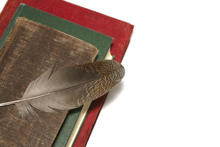 Old books and feather on a white background. Stock Photo - 9966815
