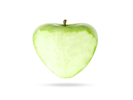 eating green apple in the shape of a heart on white photo
