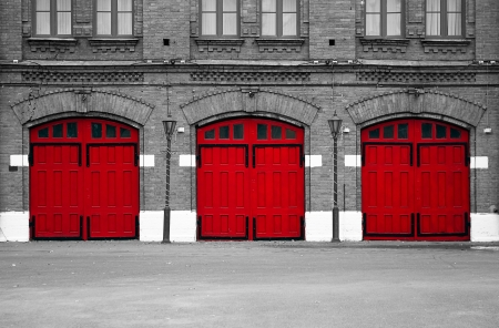 Facade of an old Fire Station in black and white with red doors.