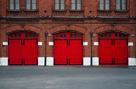 Facade of an old Fire Station with red doors. Stock Photo