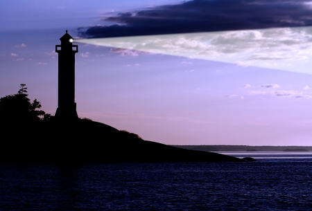 Silhouette of a  lighthouse at the sunrise. photo