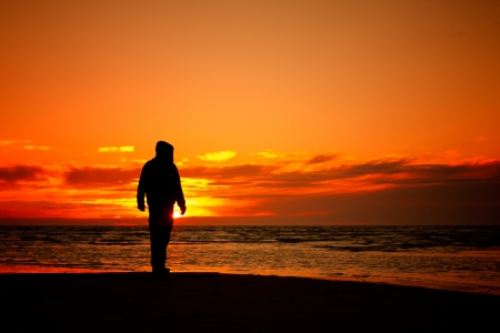 young man on a beach at sunset Stock Photo
