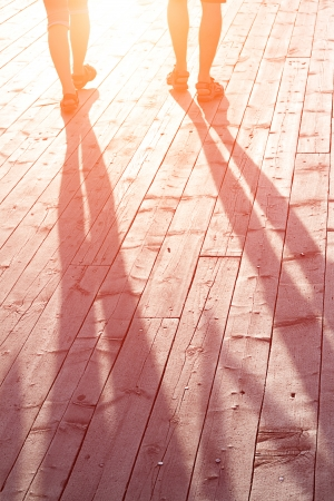 good weather: couple of lovers on a wooden bridge at sunset Stock Photo