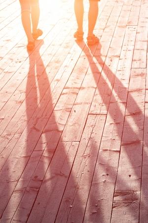 silhouettes lovers: pareja de amantes en un puente de madera al atardecer Foto de archivo