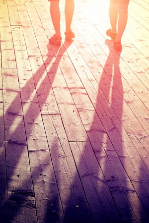 love and travel concept - couple of lovers on a wooden bridge at sunset in summer