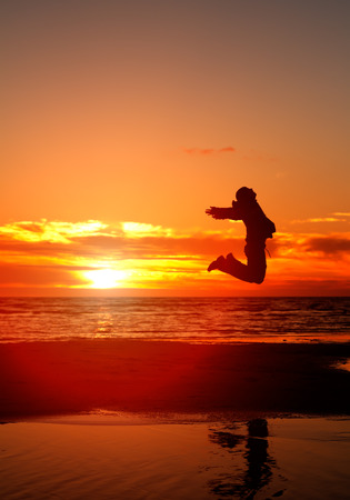 happy man jump on a beach at sunset photo