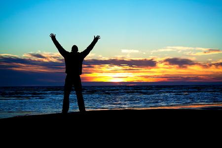 sun worship: young man hands up on a beach at sunset