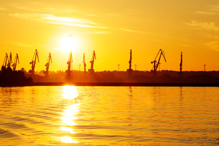 dockside: sea dock with tall cranes at sunrise, orange color tone of image Stock Photo