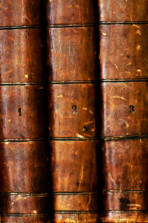 spines of hardcover old books, volume one, two and three