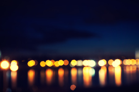defocused street lamps and reflection on a water, night city life photo