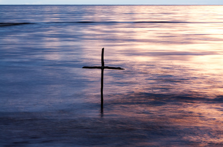 símbolo do batismo, uma cruz de madeira no rio Jordão