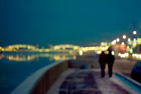 defocused image of a night city life: lovers, boke, traffic lights