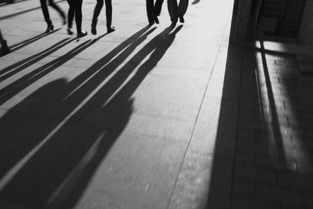 siluetas: silhouettes of people on cobblestone pavement at sunset, black and white