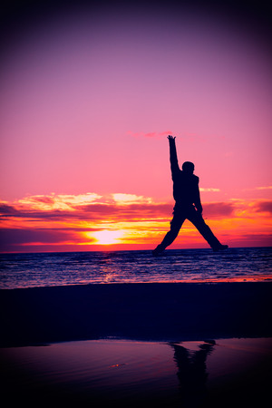 happy man jump on a beach at sunset