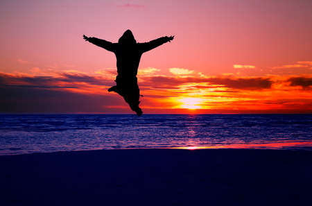 siluetas: happy man jump on a beach at sunset