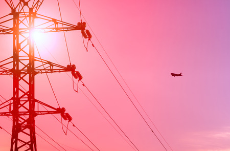 siluetas: airplane and power line at sunset Stock Photo