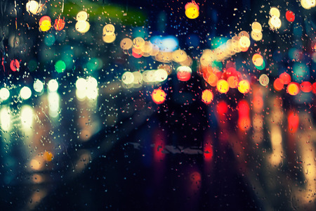 city scene: night city life through windshield: cars, lights and rain