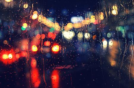 kropla deszczu: Życie nocne miasta przez przednią szybę: samochody, światła i deszczu, w stylu archiwalne stock Zdjęcie Seryjne